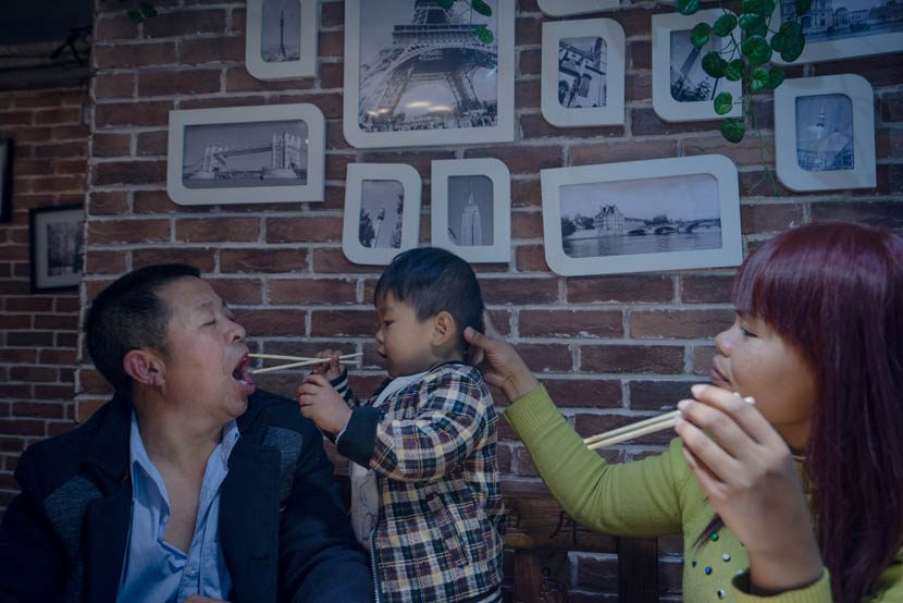 Sophorn and Zhang Chunfa's son plays with chopsticks in a restaurant, Zhengzhou, Henan province, March 29, 2016. Cong Yan for Sixth Tone
