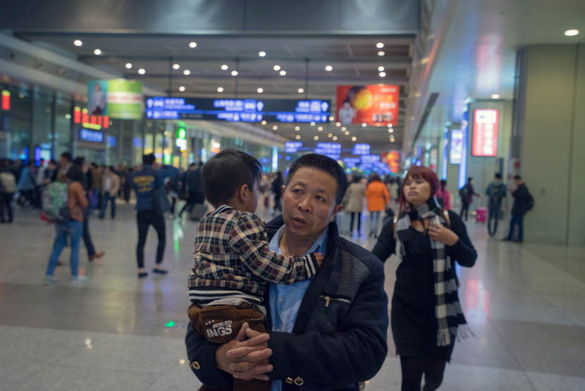 Zhang Chunfa holds his son as Sophorn rushes to catch her flight, Shanghai, March 30, 2016. Cong Yan for Sixth Tone