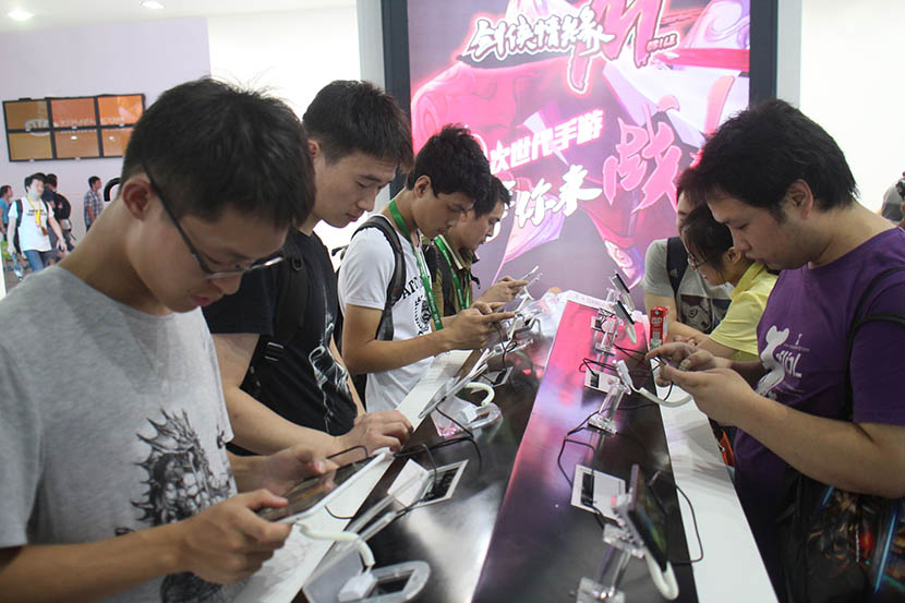 People playing games on mobile phones during a digital entertainment expo in Shanghai, Aug. 2, 2014. Xing Yun/VCG