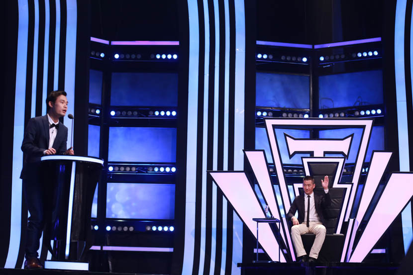 Comedian Zhang Quandan tells jokes at the podium as Zhou Jie raises his hand during the first episode of 'Roast Convention,' Shanghai, June 9, 2016. Courtesy of 'Roast Convention'