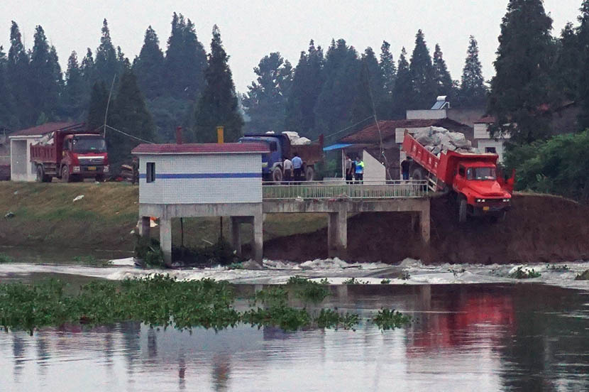 A truck carrying boulders teeters precariously on the edge of the collapsed dike in Huarong County, Hunan province, July 10, 2016. Feng Jiayun/Sixth Tone
