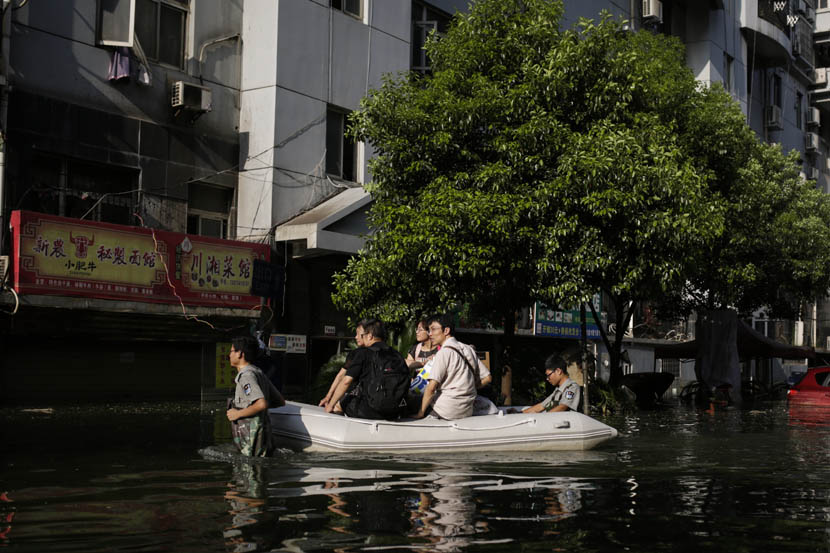 Security guards guide a raft carrying residents of the Nanhu Elegant Garden residental community, Wuhan, Hubei province, July 10, 2016. Han Meng/Sixth Tone