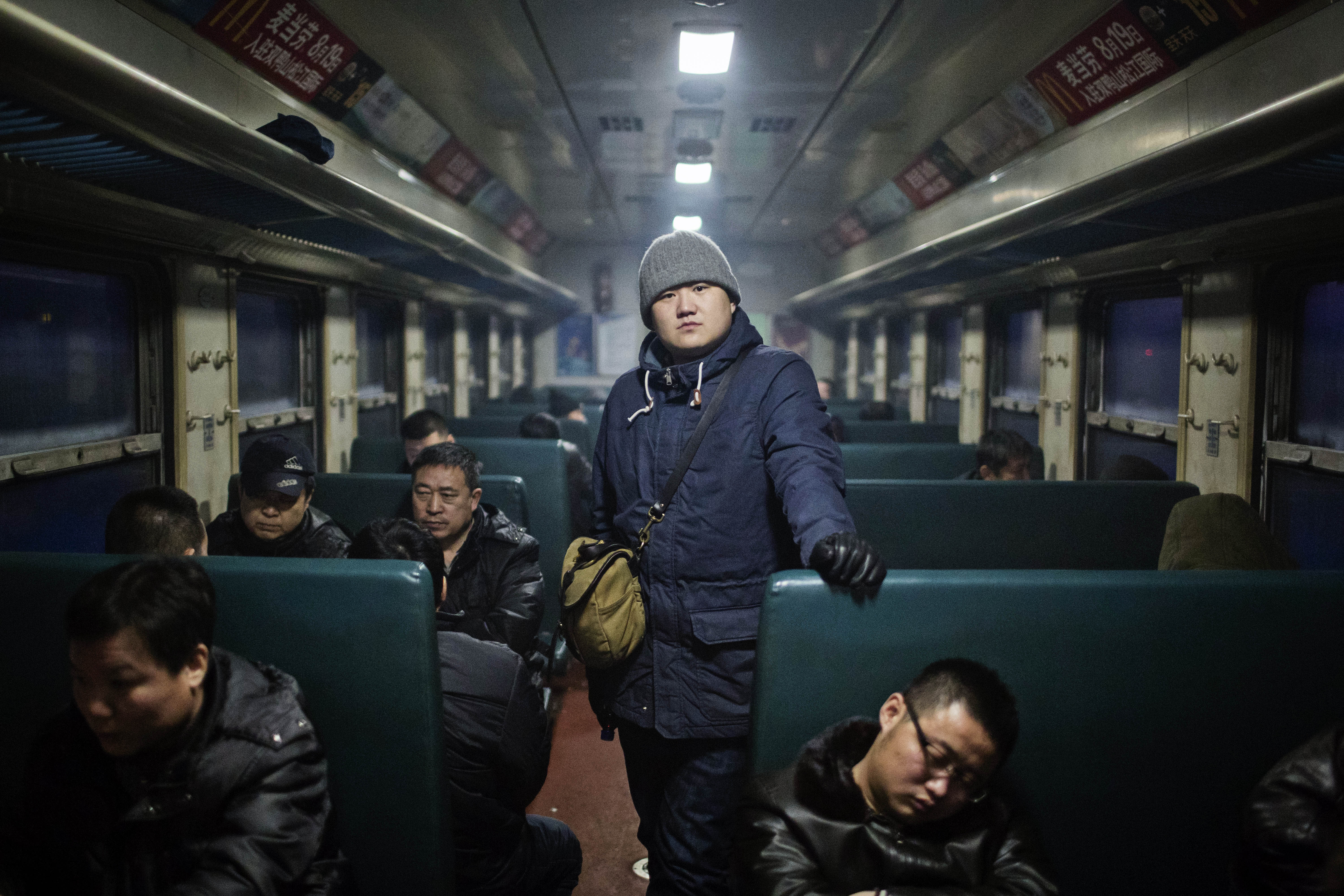 Zhang Tianqi stands in the aisle of a commuter train that takes miners to and from the mining area, Jan. 21, 2016. In today's mining communities, faces as young as Zhang's are few and far between. Zhou Pinglang/Sixth Tone