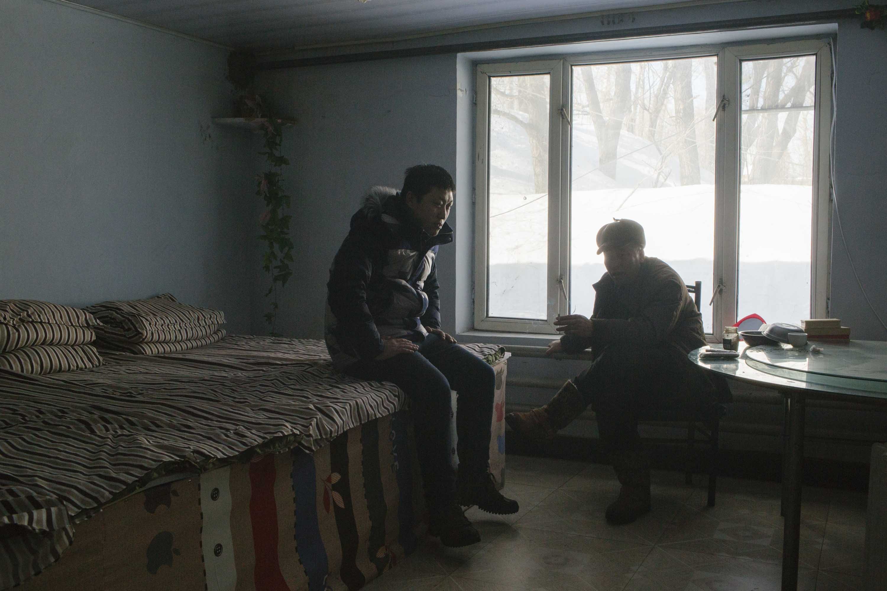 Xia Yan and his father chat with each other the day after Zhang Tianqi's wedding, Shuangyashan, Jan. 27, 2016. Xia's father opened a small hotel for miners after he lost his high-powered mining position following a cerebral infarction. Zhou Pinglang/Sixth Tone