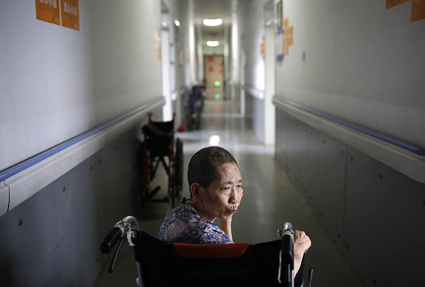 A woman sits in a wheelchair in the hallway of Songtang Hospice, Beijing, July 19, 2016. Han Meng/Sixth Tone