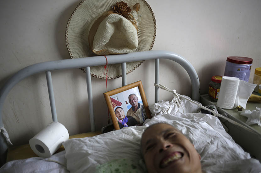 A woman lies in bed with a photo of her husband behind her at Songtang Hospice, Beijing, July 19, 2016. Her husband visits the hospice every day. Han Meng/Sixth Tone