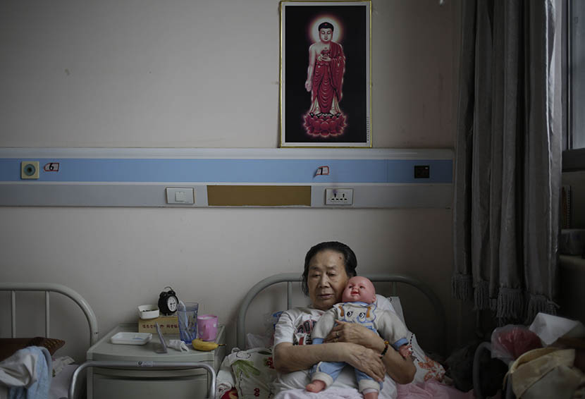 A woman holds a doll donated by a hospice volunteer at Songtang Hospice, Beijing, July 19, 2016. Han Meng/Sixth Tone