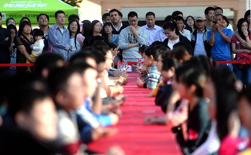 People watch single women and men chatting during a speed dating event in Jinan, Shandong province, Sept. 12, 2015. Wen Lu/VCG