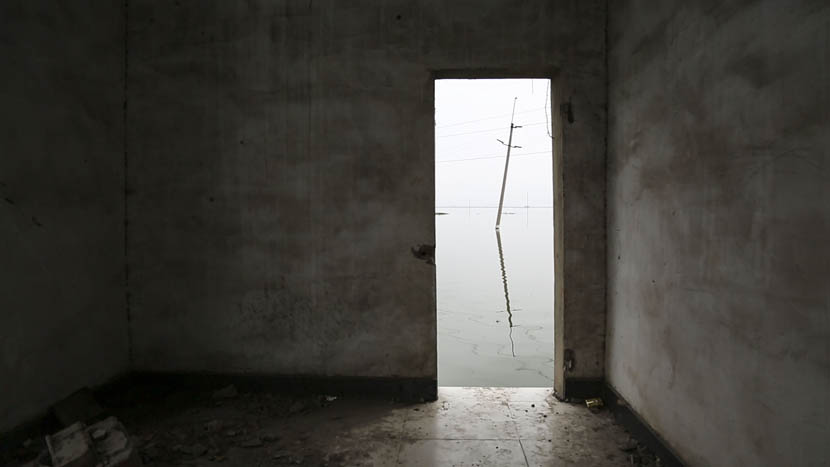 A utility pole is visible from the doorway of a house inundated by water in Huainan City, Anhui province, July 7, 2016. Wu Yue/Sixth Tone