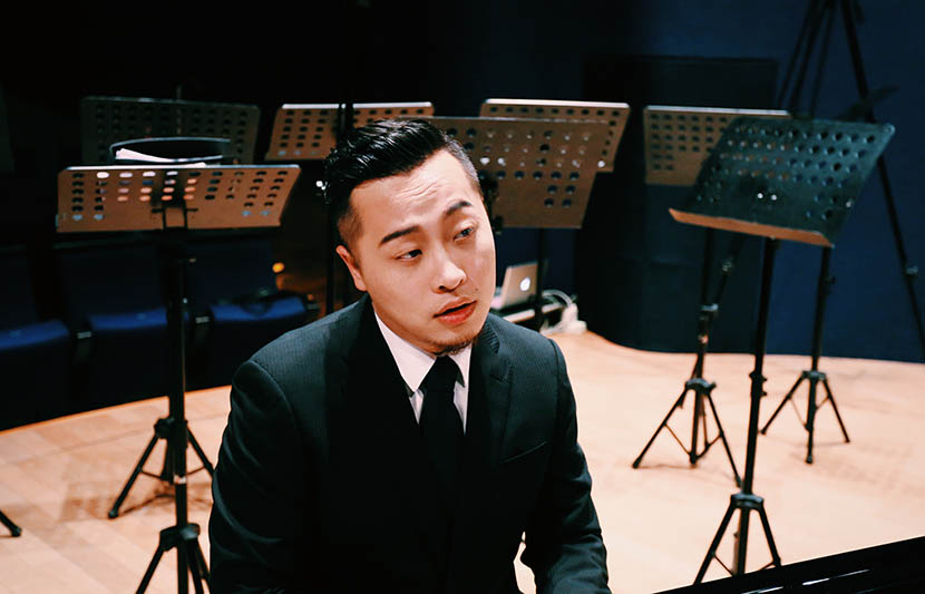 Jin Chengzhi, conductor of the Rainbow Chamber Choir, poses for a photo in a concert hall. Courtesy of Rainbow Chamber Choir