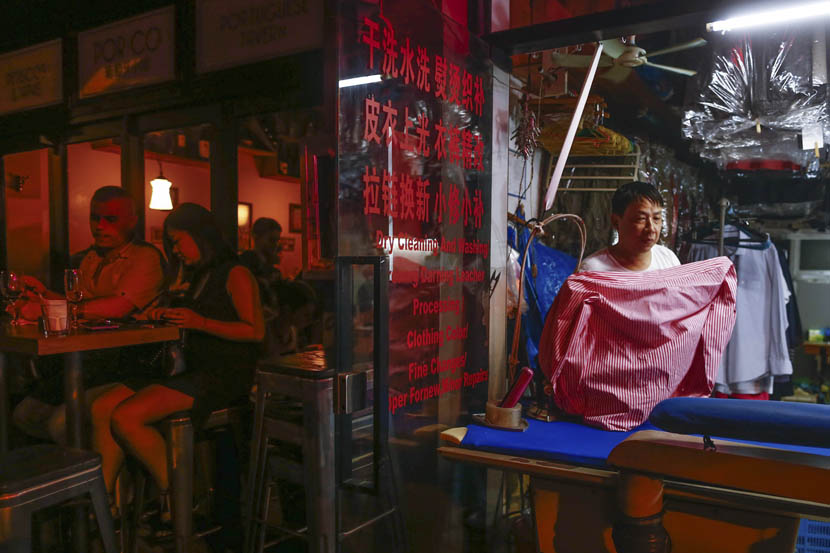The owner of a dry-cleaning shop works while the crowds outside reach a crescendo at 11 p.m., Shanghai, July 15, 2016. Zhang Ruiqi/IC