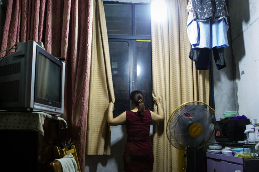 A resident on Yongkang Lu closes the curtains on the crowds beneath. Shanghai, July 16, 2016. Wei Yi/Sixth Tone