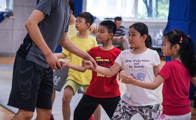 A fencing coach instructs children at the Wang Lei International Fencing Club in Shanghai, Aug. 3, 2016. Zhou Yinan/Sixth Tone