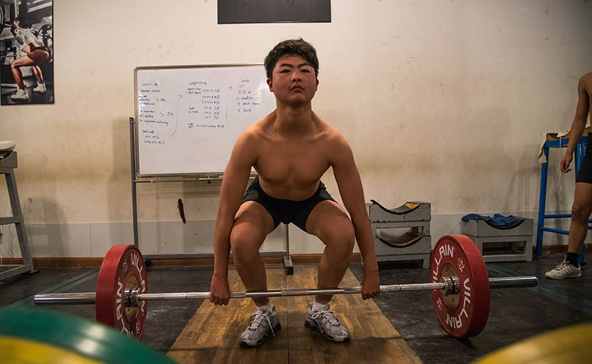 A man lifts weights at Venus Weightlifting Club in Shanghai, Aug. 4, 2016. Zhou Yinan/Sixth Tone
