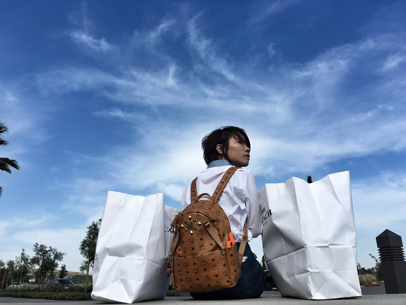 Yao, with two bags of merchandise, rests near the parking lot of an outlet mall in San Francisco, California, U.S., May 28, 2016. Wu Jiaxiang for Sixth Tone