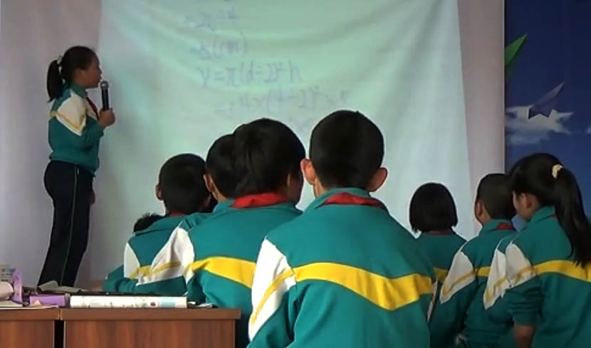A screenshot from a 'san yi san tan' demo class video shows a student giving a presentation to her peers at Fanshan Primary School in Zhuolu County, Hebei province, 2015. From the official website of the county's education bureau.