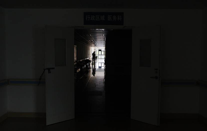 A man stands in the hallway of the maternity ward at Second People's Hospital in Chongming District, Shanghai, July 22, 2015. Five days prior, an infant born with a cleft lip was killed here by his grandfather. Yong Kai/Sixth Tone