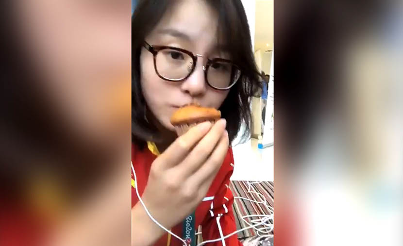 A screenshot from a live video stream on Ingkee shows Fu Yuanhui eating a cupcake.