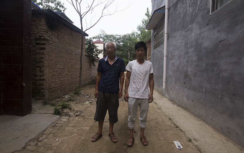 Song Xianzhong poses with his son Song Pengpeng outside their home in Songzhuang, Henan province, Aug. 1, 2016. Owen Churchill/Sixth Tone