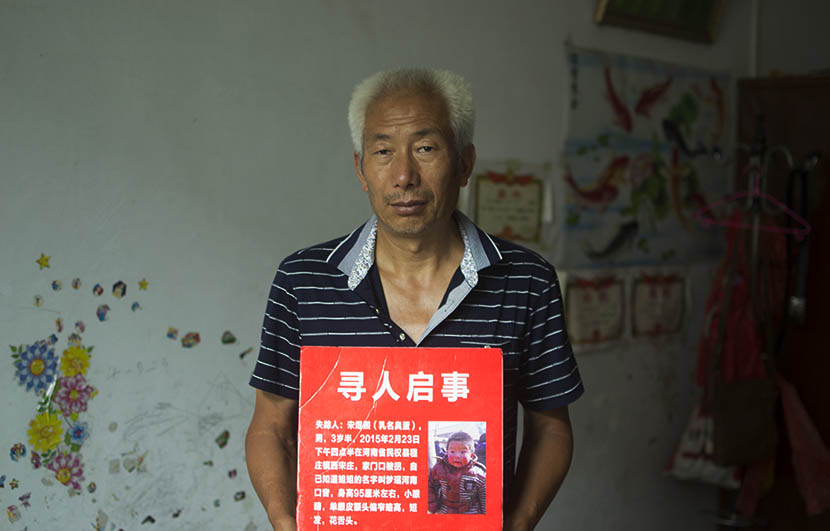 Song Xianzhong poses at home with the missing persons notice of his grandson Song Yuxi, Songzhuang, Henan province, Aug. 1, 2016. Owen Churchill/Sixth Tone