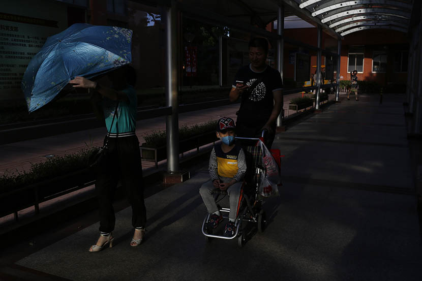 The Wu family walks to the hospital every day for Hao's treatment, Shanghai, Aug. 7, 2016. Wu Yue/Sixth Tone