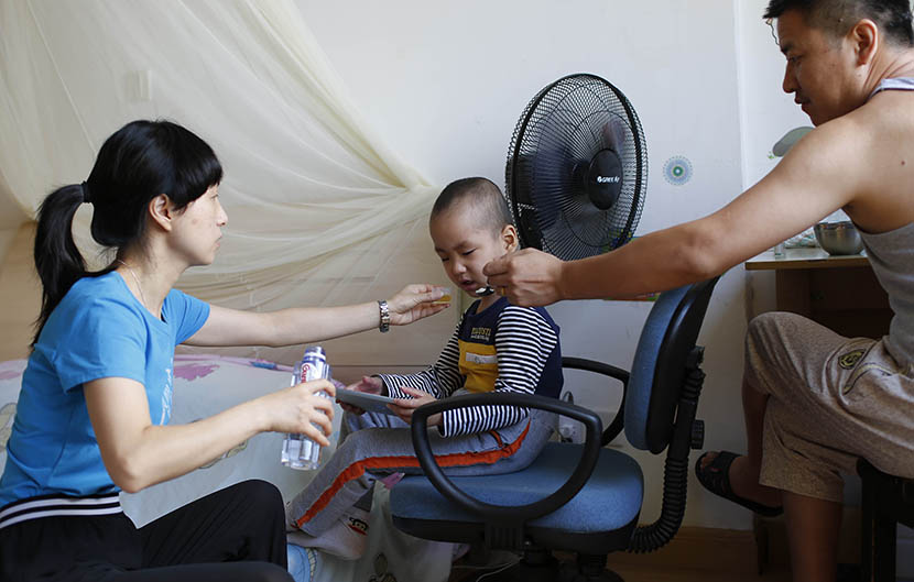 Hao's parents feed him breakfast and medicine in the morning before their daily trip to the hospital, Shanghai, Aug. 6, 2016. Wu Yue/Sixth Tone
