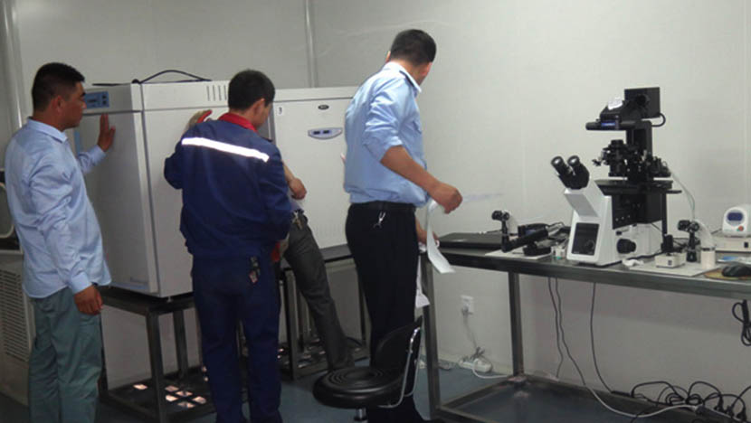 Law enforcement officers check equipment at an illegal lab that provided surrogacy services in Shanghai, May 2016. Courtesy of Shanghai Songjiang District Health Inspection Bureau.