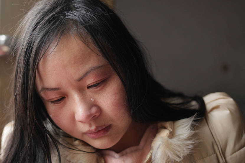 A tear runs down Lin Chunhong's face as she recalls her childhood in Linyi, Shandong province, March 8, 2016. Her adoptive mother remarried three times, and they were often destitute. Han Meng/Sixth Tone
