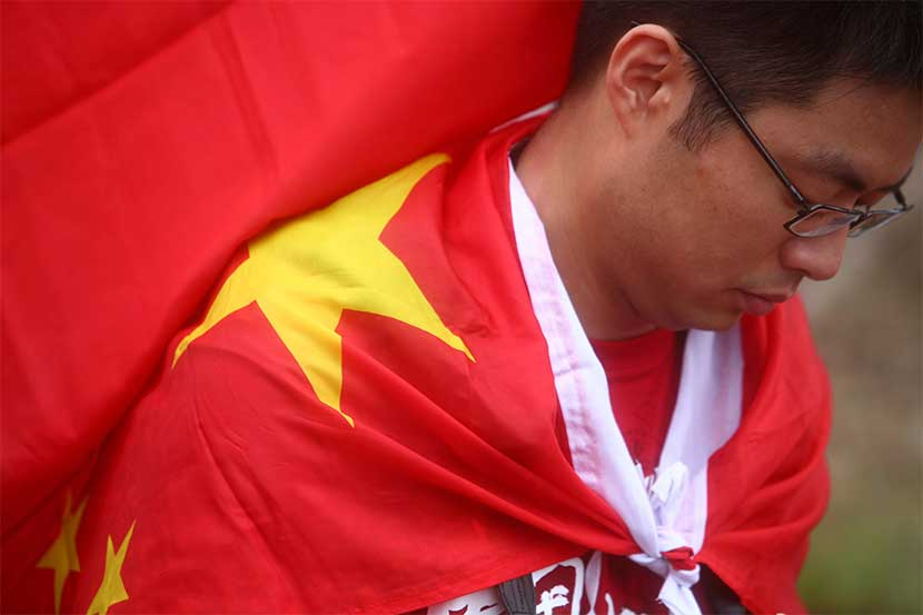 A man wears a Chinese national flag to go see the 2008 Beijing Games Olympic Torch Relay in Hong Kong, May 2, 2008. Protests surrounding the torch relay were a major topic on Anti-CNN. Eric Tsang/VCG