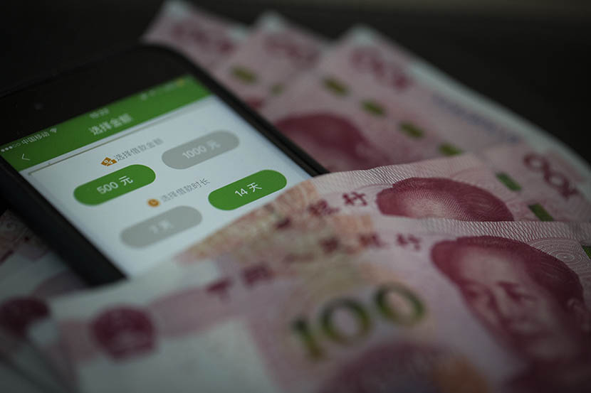 A photo illustration shows the CashBUS app on a cellphone nestled among hundred-yuan banknotes. Yang Shenlai/Sixth Tone