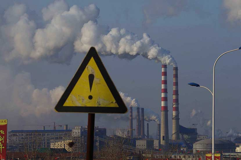 A warning sign with chimneys visible in the background, Rizhao, Shandong province, Feb. 19, 2015. Guo Lei/VCG