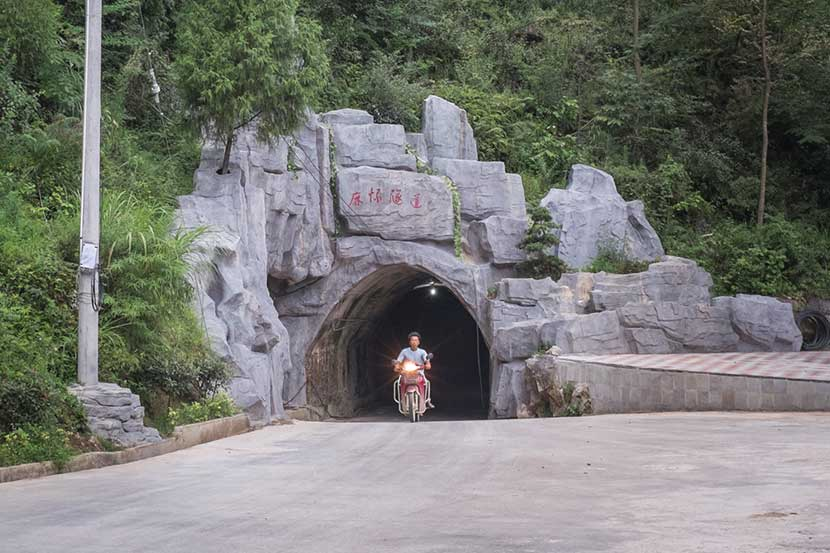 A man rides a motorcycle through the tunnel in Mahuai Village, Guizhou province, Aug. 27, 2016. Denise Hruby/Sixth Tone