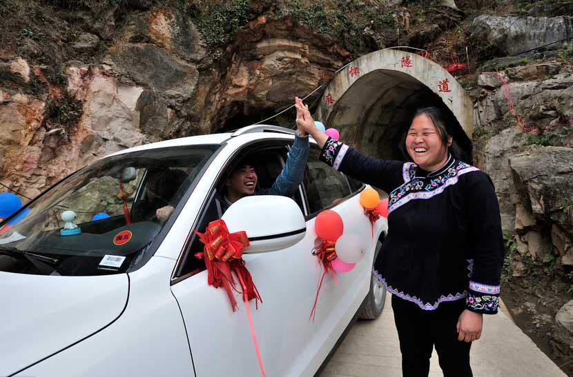 Deng Yingxiang gives a driver a high-five at the entrance to the tunnel in Mahuai Village, Jan. 18, 2016. Xu Fengshan/IC