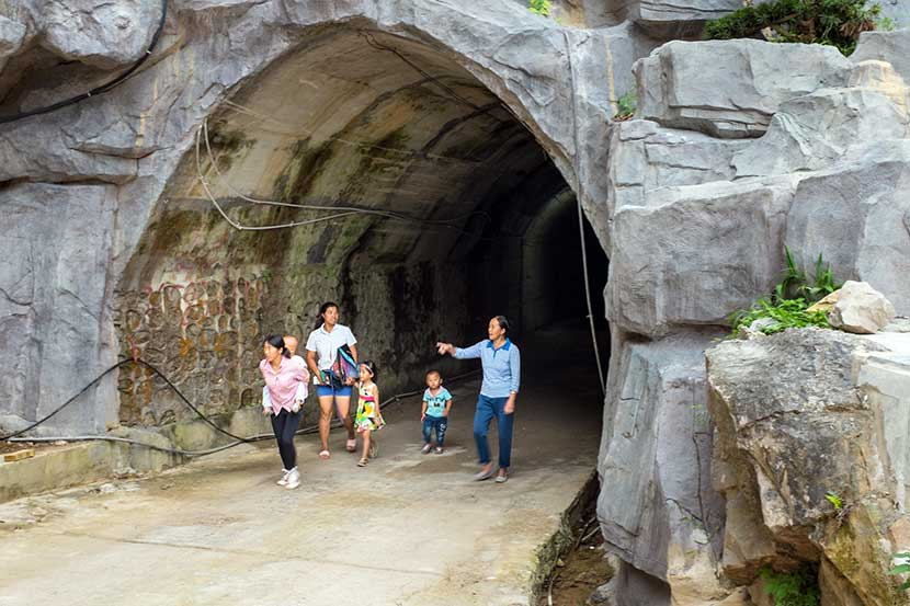 People walk through the tunnel in Mahuai Village, Guizhou province, Aug. 27, 2016. Denise Hruby/Sixth Tone