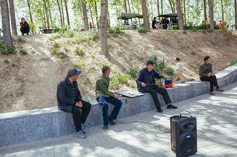 Local residents sit in a park near Baiyang Lake in Anxin County, Hebei province, April 11, 2017. Wu Huiyuan/Sixth Tone