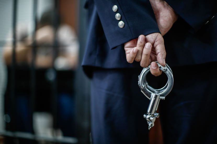 A policeman holds a pair of handcuffs in Shanghai, Nov. 28, 2014. Yang Yi/Sixth Tone