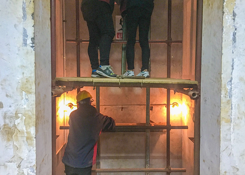 Students majoring in elevator maintenance repair parts inside an elevator shaft during a class in Shanghai, March 21, 2017. Fu Danni/Sixth Tone
