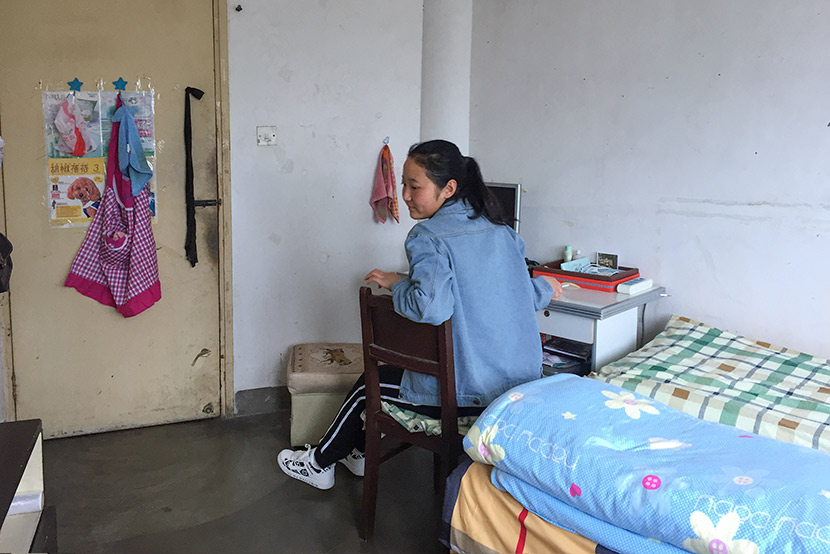 Li Xiumao sits in her bedroom at her elevator company's employee housing unit in Shanghai, April 7, 2017. Fu Danni/Sixth Tone