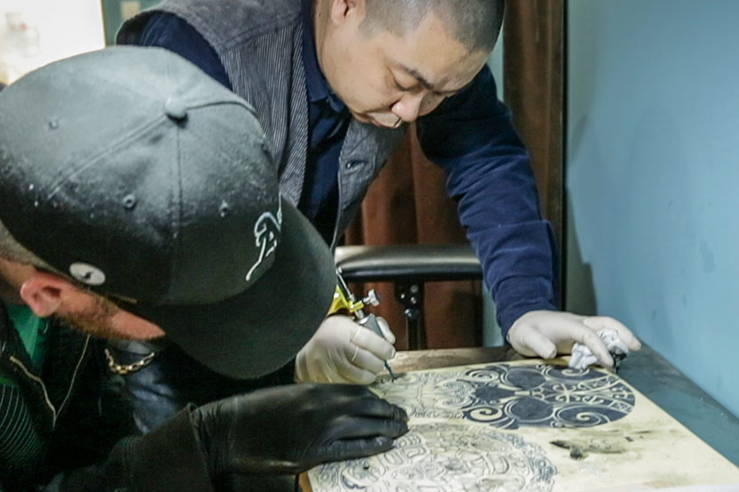 Tattoo artist Shao Gang demonstrates the process of tattooing a pattern to apprentice Daniel Whitford in Shanghai, March 25, 2017. Tang Xiaolan/Sixth Tone