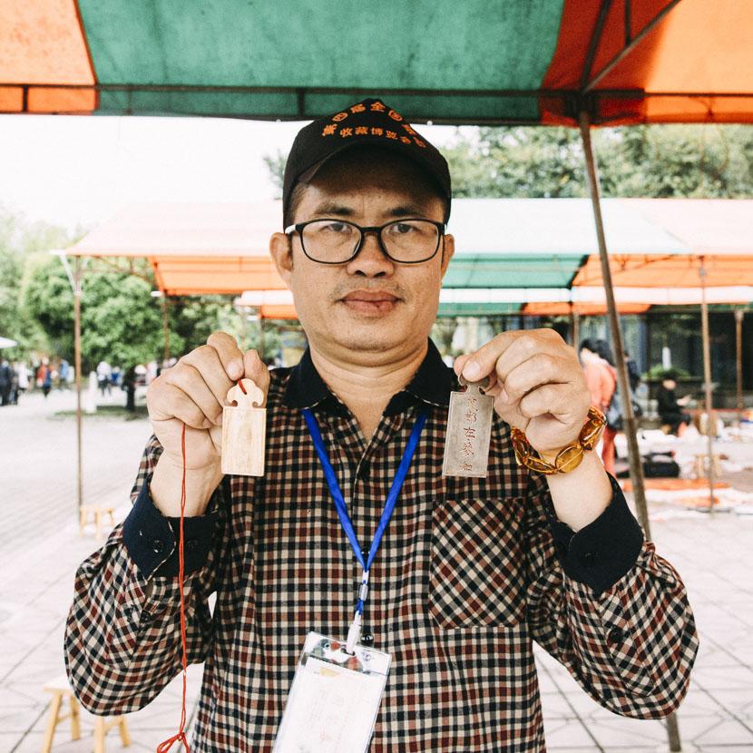 Zhuo Yijian holds up a set of Qing Dynasty metal plaques in Anren Town, Dayi County, Sichuan province, April 8, 2017. Barclay Bram Shoemaker/Sixth Tone