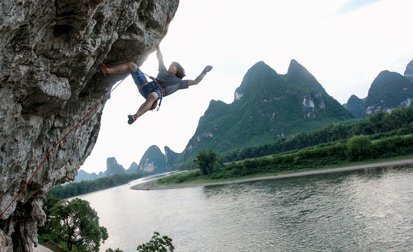 A climber scales a rock face in Yangshuo County, Guangxi Zhuang Autonomous Region, May 19, 2012. Liu Jiaoqing/VCG