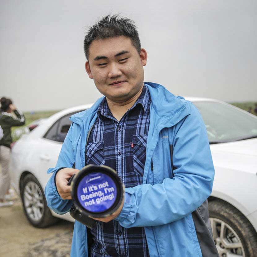 Sun Shengdi, who works in the finance industry, displays his lens cap outside Shanghai's Pudong International Airport, May 5, 2017. Daniel Holmes/Sixth Tone