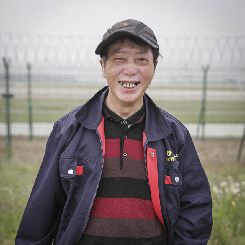 63-year-old Ye Yinggen, a migrant worker from Jiangxi province working on Pudong's fifth runway, poses for a photo outside Shanghai's Pudong International Airport, May 5, 2017. Daniel Holmes/Sixth Tone