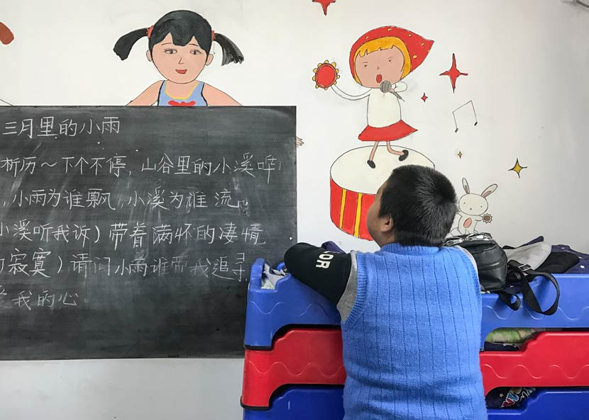 A student looks at the blackboard in a classroom at the Lingxing Community Service Center in Taiyuan, Shanxi province, April 5, 2017. Wang Yiwei/Sixth Tone