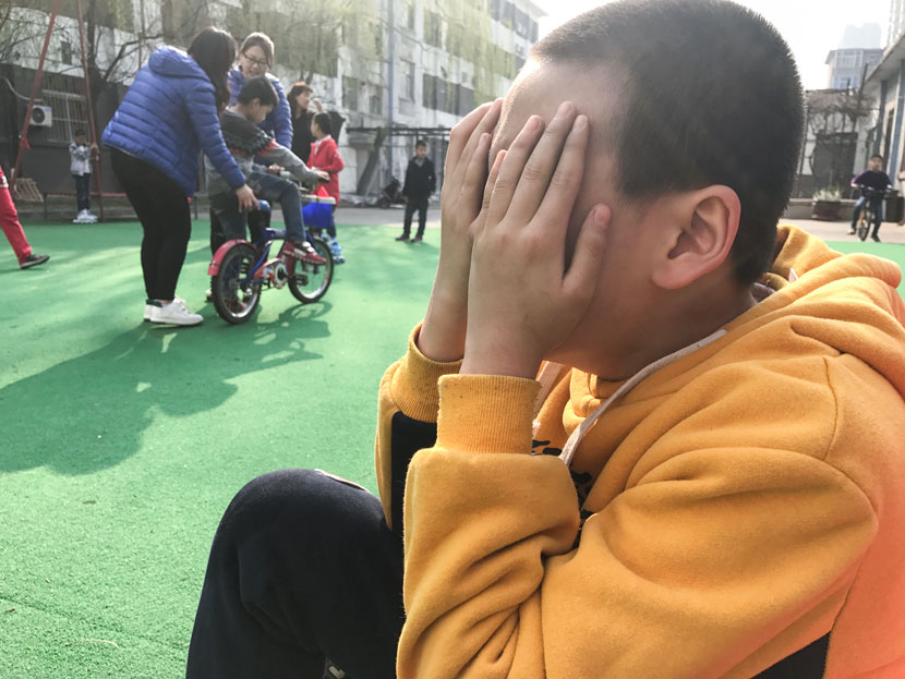 A student covers his face with his hands on the playground at the Lingxing Community Service Center in Taiyuan, Shanxi province, April 5, 2017. Wang Yiwei/Sixth Tone
