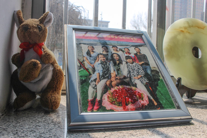 A photo of teachers at the Lingxing Community Service Center, including Li Xiaojiao (front row, center), sits on a windowsill in Taiyuan, Shanxi province, April 5, 2017. Wang Yiwei/Sixth Tone