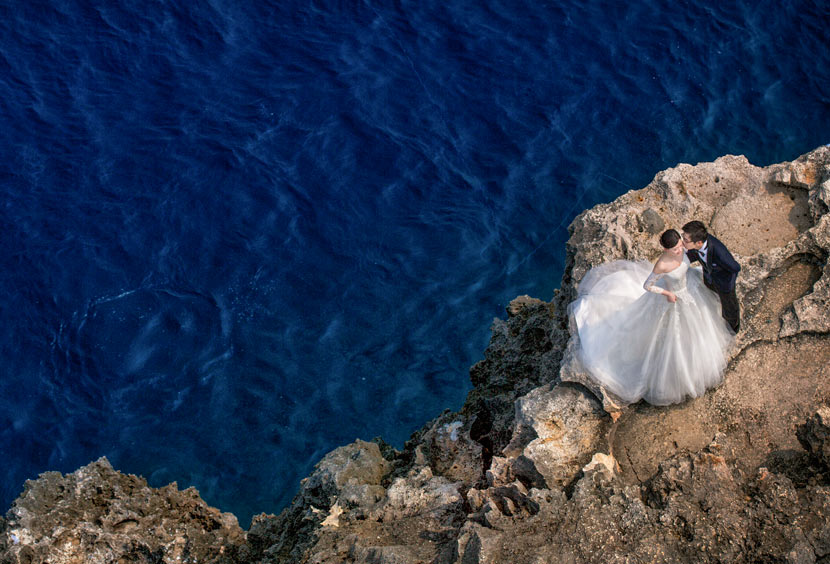 A couple poses for a wedding photo on a seaside cliff in Okinawa, Japan, April 3, 2016. Courtesy of Guo Kun