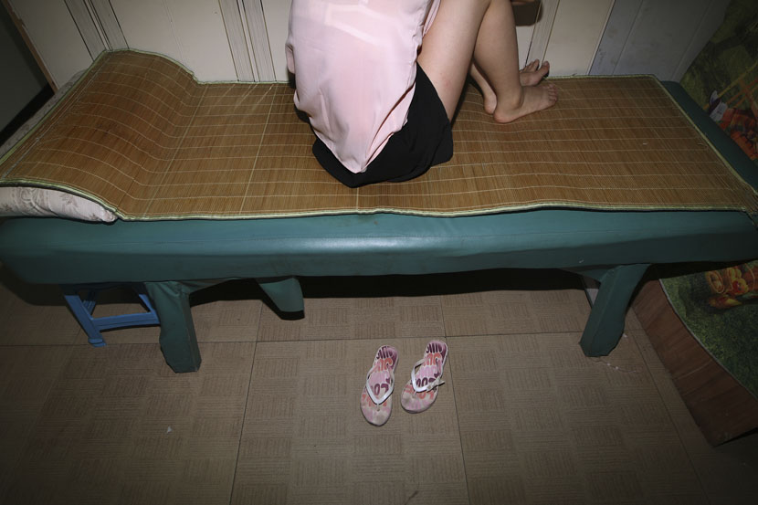 A sex worker sits on her bed in Hangzhou, Zhejiang province, Sept. 17, 2010. Li Qin/VCG