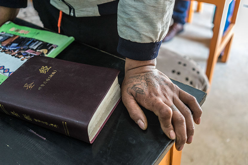 A faded tattoo of a rose can be seen on Cao Yufa's hand during morning prayers at the Gospel Rehabilitation Center in Baoshan, Yunnan province, March 19, 2017. Thomas Cristofoletti for Sixth Tone