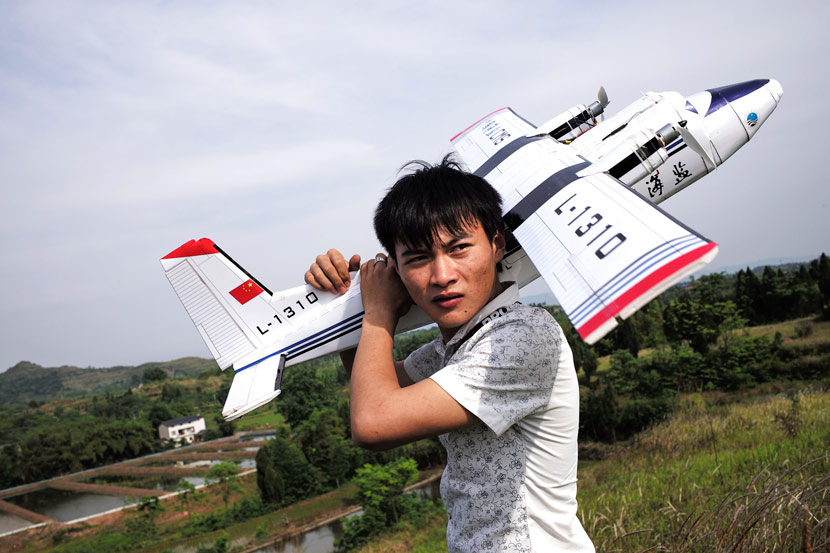 Hu Bo carries his model Y-12 aircraft after taking it out for a flight in Dazu County, Chongqing, May 16, 2017. Wu Yue/Sixth Tone
